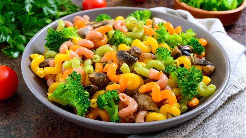 cavatappi colored pasta with broccoli and mushrooms