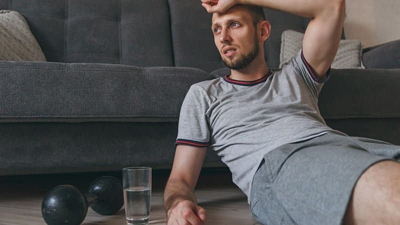 exhausted man sitting on floor breathing and resting