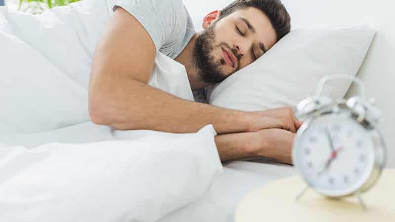 handsome bearded man sleeping in bed