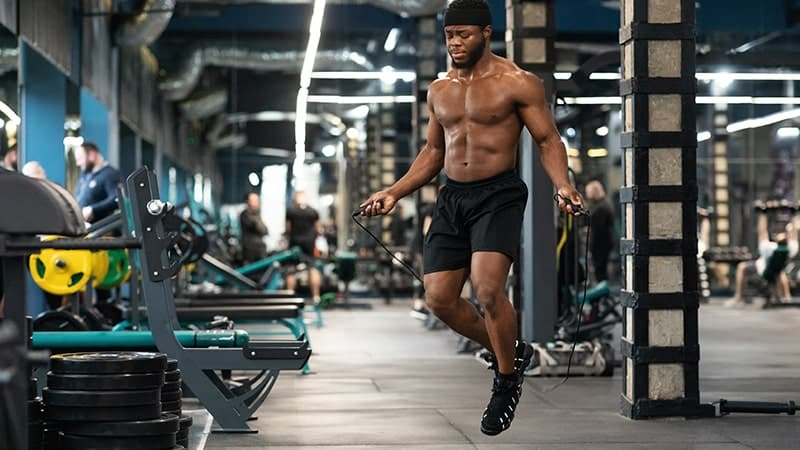 shirtless muscular african man jumping with skipping rope