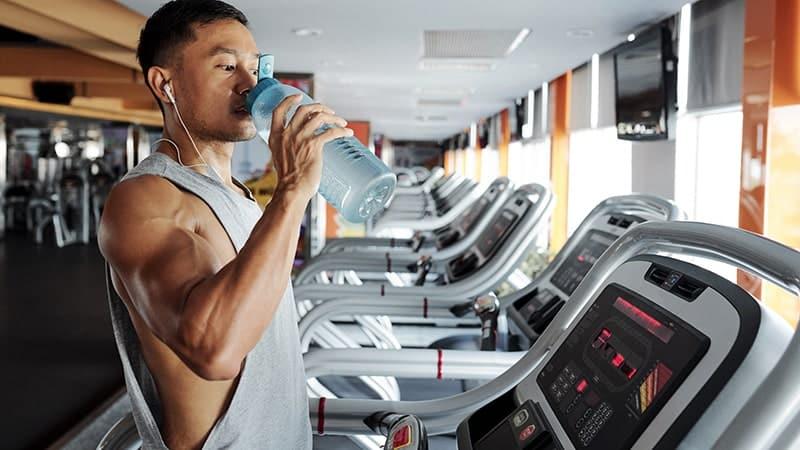 sportsman drinking water on the treadmill