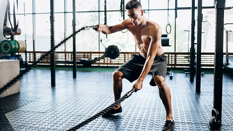 young athletic man doing HIIT at the gym with ropes