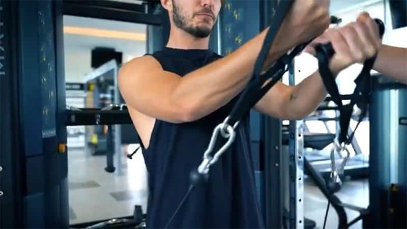 young man at the gym using the cable machine